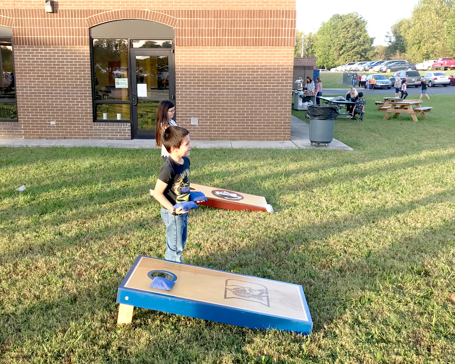 CHRISTIAN KIMMONS and Marianna Waldroup enjoy a game of cornhole during Blythe-Bower Elementary School's recent Fall Harvest Hoedown.