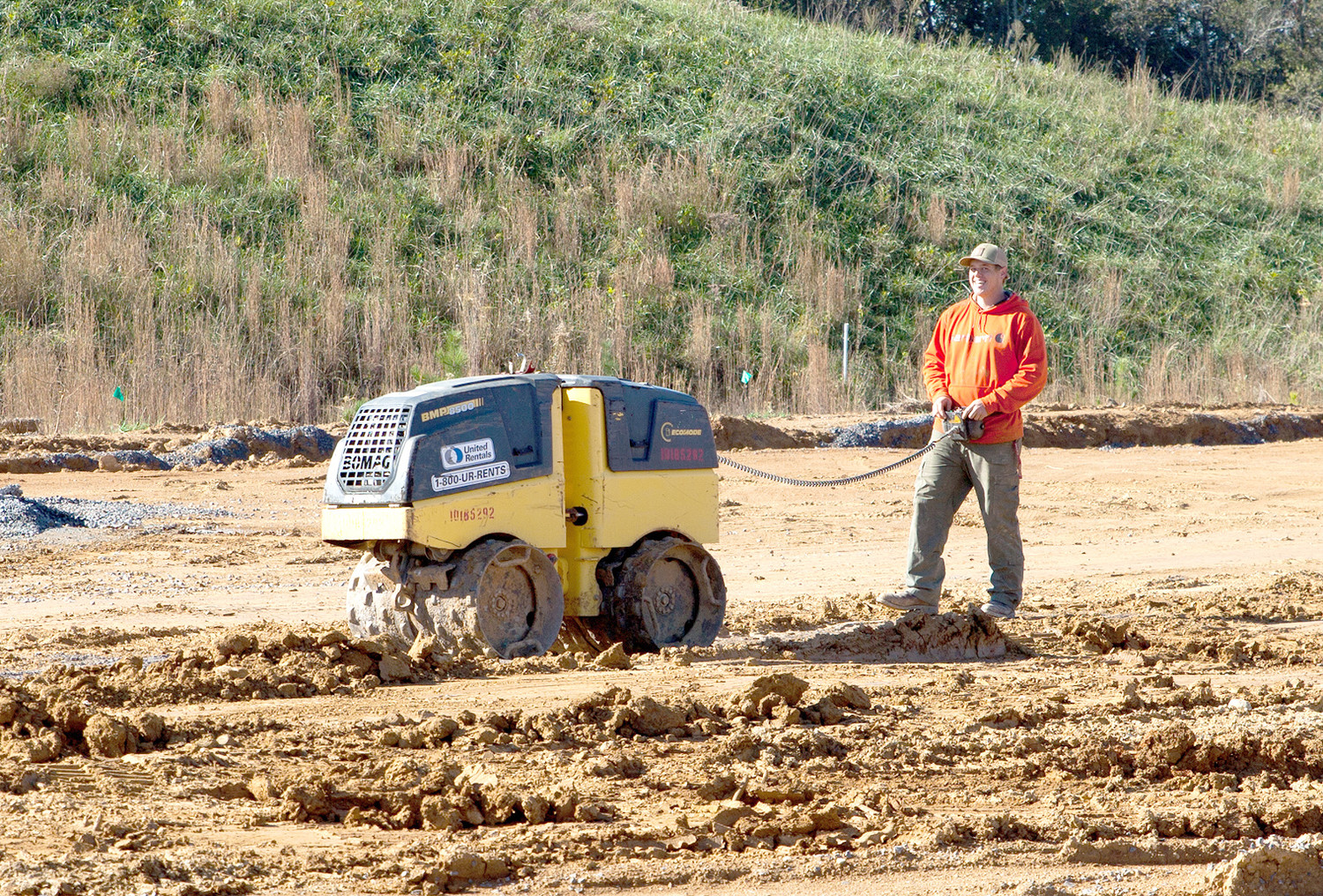 A CONSTRUCTION WORKER uses a remotely operated tool to compact the soil and rock around a newly installed water line at the site of the new Cleveland elementary school.