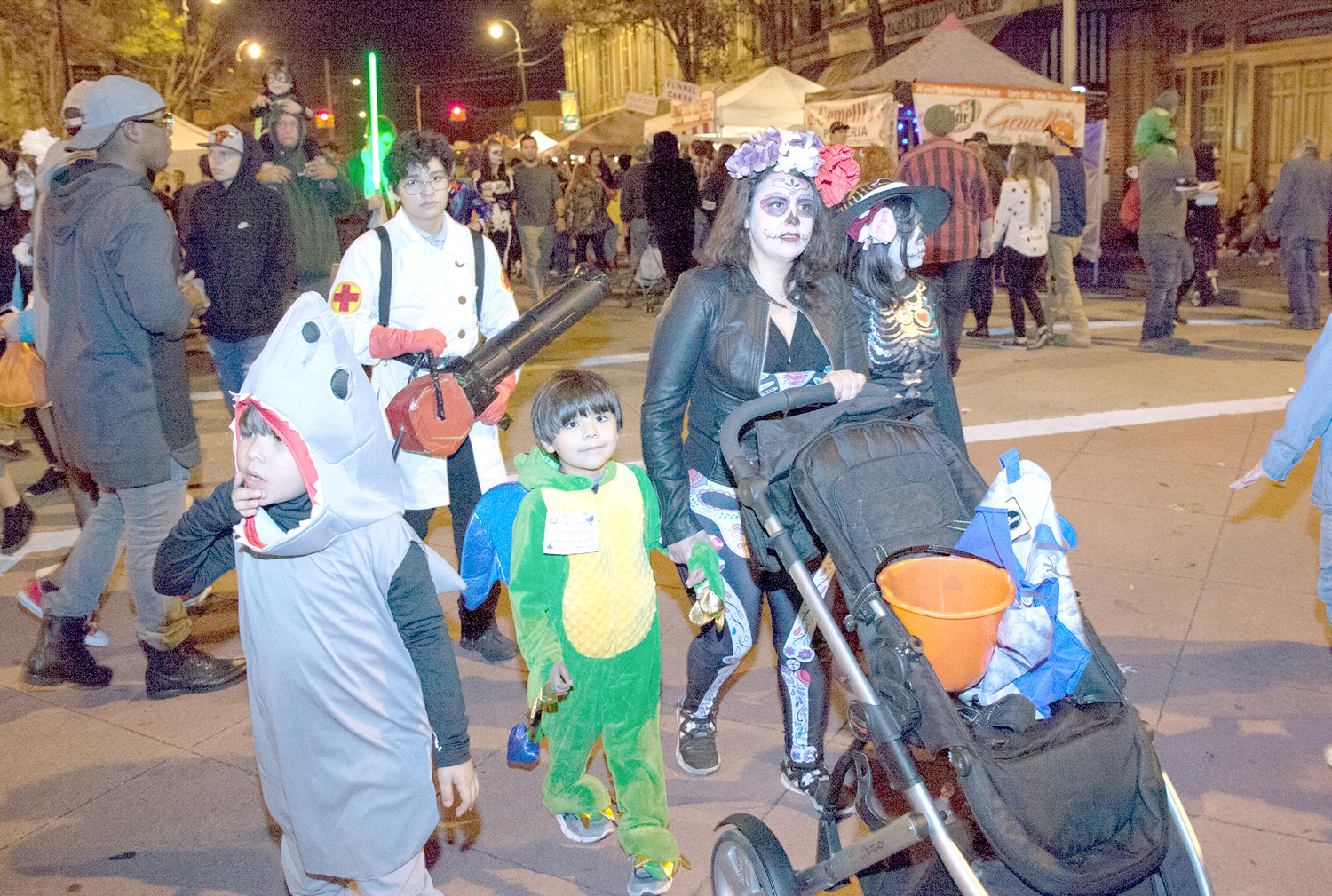 THIS FAMILY: a shark, a dragon, a medic and two ladies dressed for Dia de los Muertos, hunt for candy, food and fun during the Block Party.