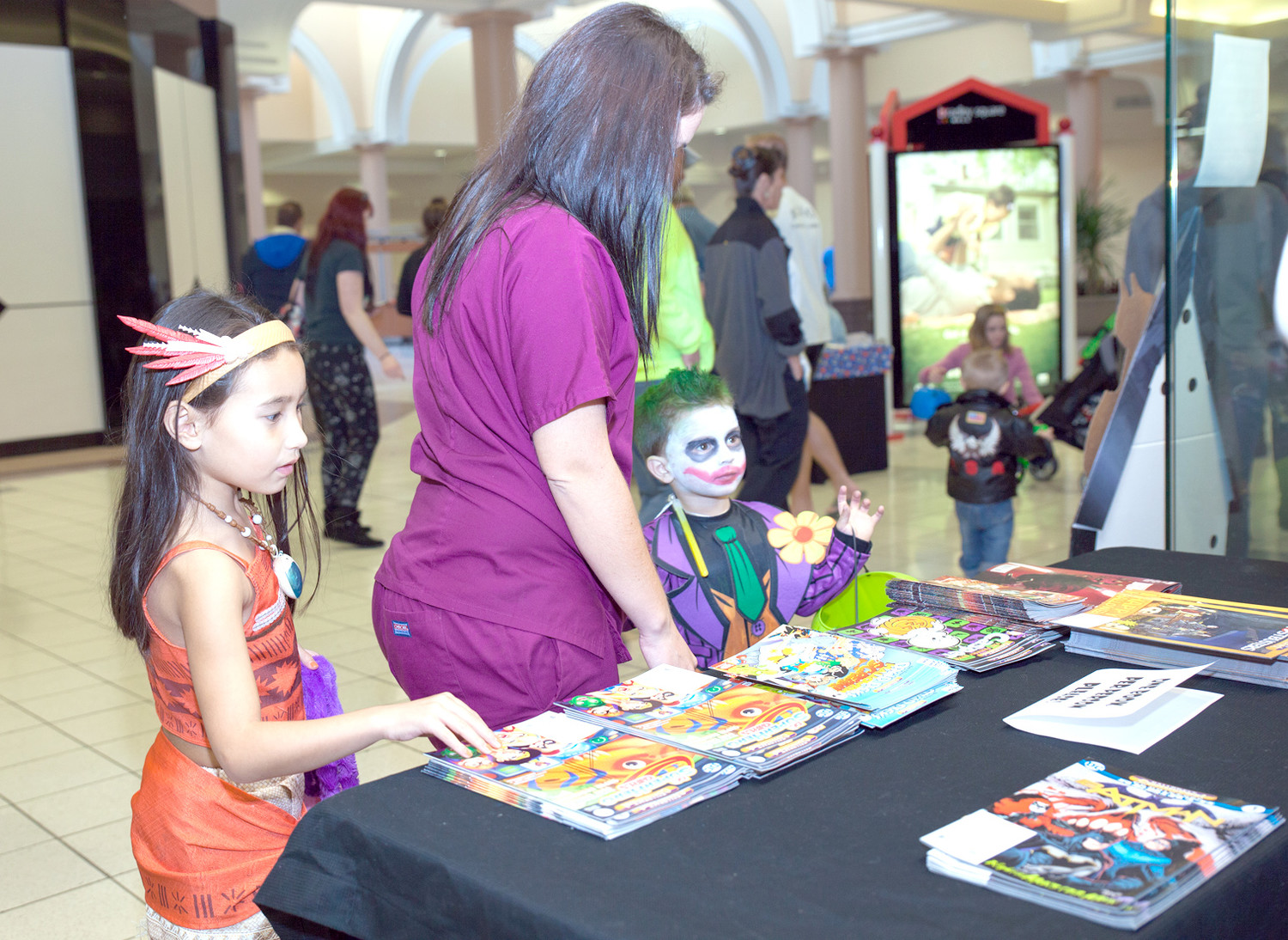 A COUPLE OF YOUNG trick-or-treaters dressed as Pocahontas and the Joker contemplate what comic book to take at Dicehead Games and Comics, during the Spooktacular Fall Festival in Bradley Square Mall.