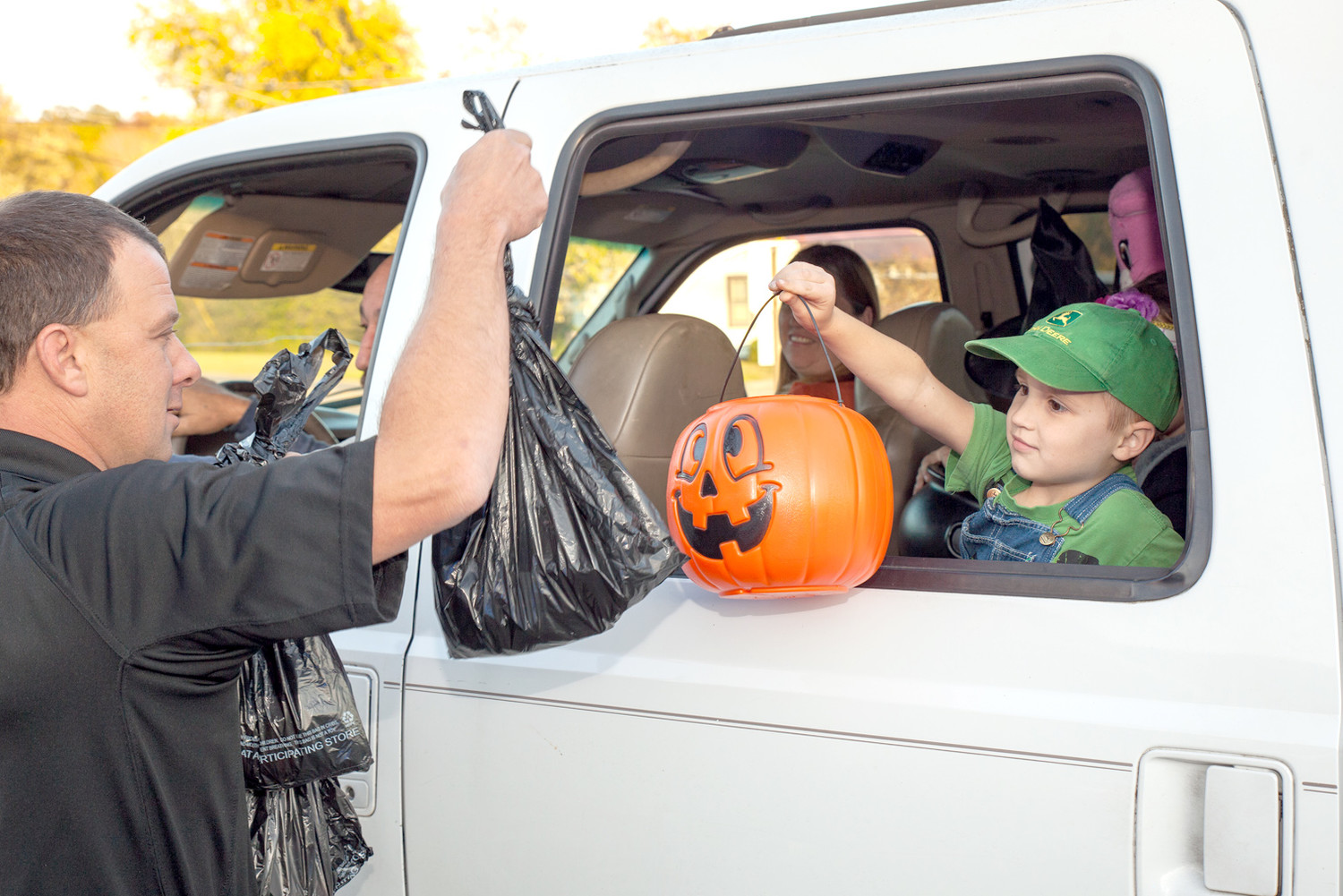 CONSTABLE WAYNE HENRY, right, continues his seven-year tradition of passing out bags of candy to trick-or-treaters by the carload at Oak Grove Elementary School on Halloween.  The trick-or-treater in this car brought a candy catcher, but it seemed to be too small to grab the bag of candy from the constable.