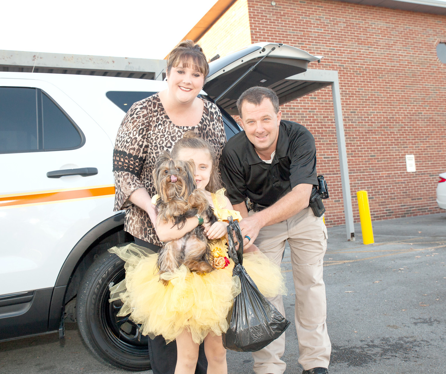"CONSTABLE WAYNE HENRY, right, and his wife, Casey, left, pose with one trick-or-treater, Reagan Robertson, dressed as Belle, holding her companion ""Beast"" for the night."