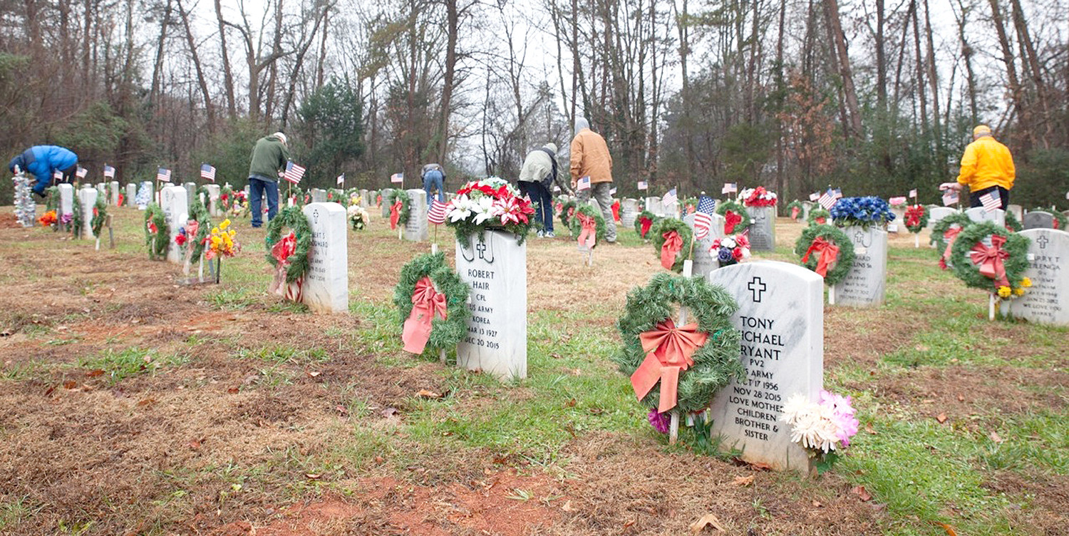 MEMBERS OF AMVETS POST 13, and others, were busy recently placing wreaths with ribbons and small U.S. flags on the graves in the veterans' section of the city's Fort Hill Cemetery.