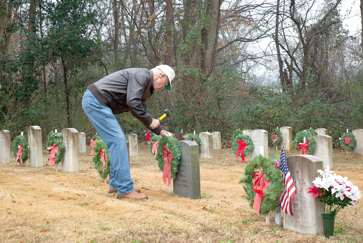 CLEVELAND'S JOHN THOMASON, who is active with several veterans organizations in Bradley County, was busy preparing a Christmas wreath and a small U.S. flag on the grave of a local veteran in Fort Hill Cemetery. More than 200 wreaths were placed in the cemetery recently.