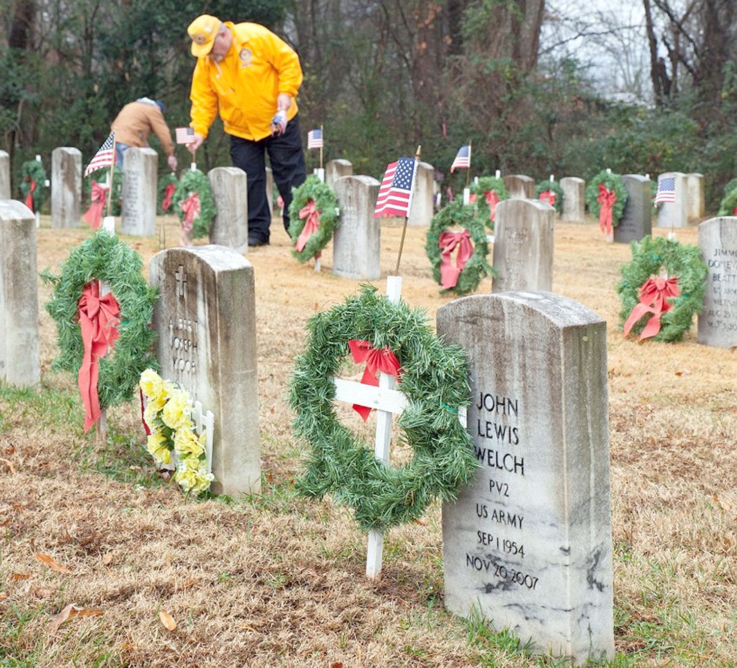 BRADLEY COUNTY's Rick Williams, and an unidentified local veteran in the background, were busy recently as they participated in AmVets Post 13's Christmas wreath ceremony in Fort Hill Cemetery. The program has been ongoing for eight years.