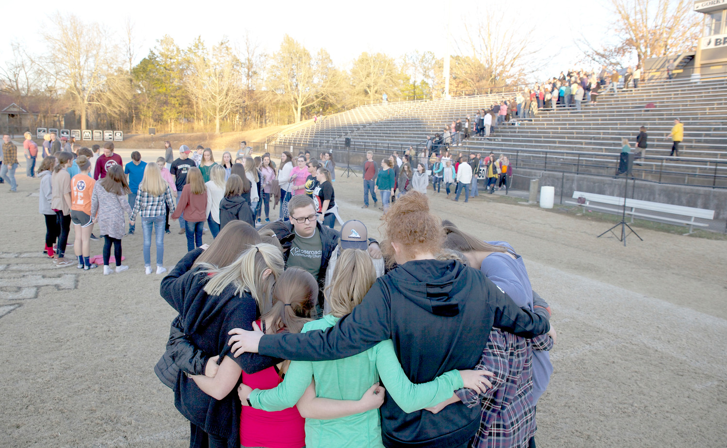 AN ORGANIZER of Sunday's Prayer Revival and recent BCHS graduate, Cade Baker, center, takes part in a small prayer circle while the rest of the attendees walk to the field for the larger prayer circle.