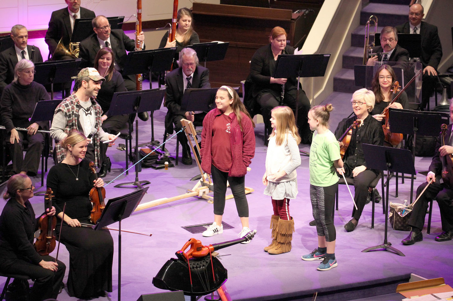 DURING THIS SEGMENT, Narrator Tator, left, relies on three lucky students to help him cue the orchestra to play certain melodies, rhythms and harmonies. From left are Tator, Klover Richardson, Michigan Avenue Elementary; Ellen Adams, Hopewell Elementary; and Anna Claire Gibson, Black Fox Elementary.