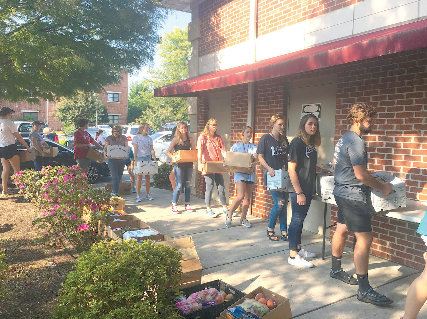 TUDENTS?line up to help prepare boxes of food to give away while participating in Lee University's Crossover effort.