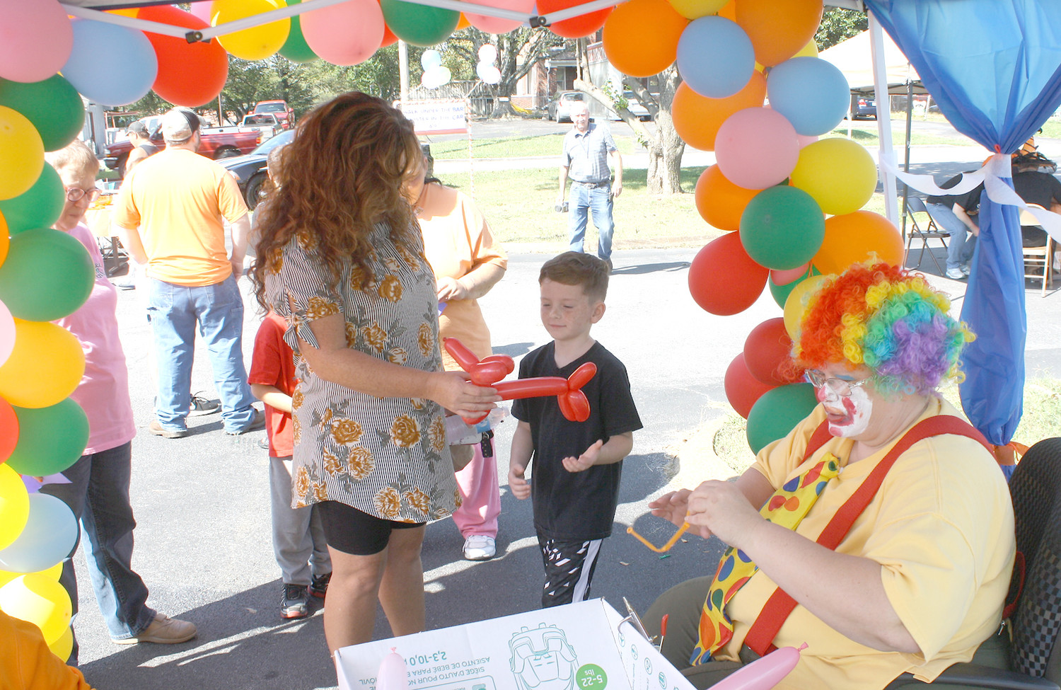 KIM MORRISON, in clown suit, delighted seven-year-old Bentley Catlett with a balloon animal at Friday's Fall Festival at the health department. The balloons were popular with the kids.