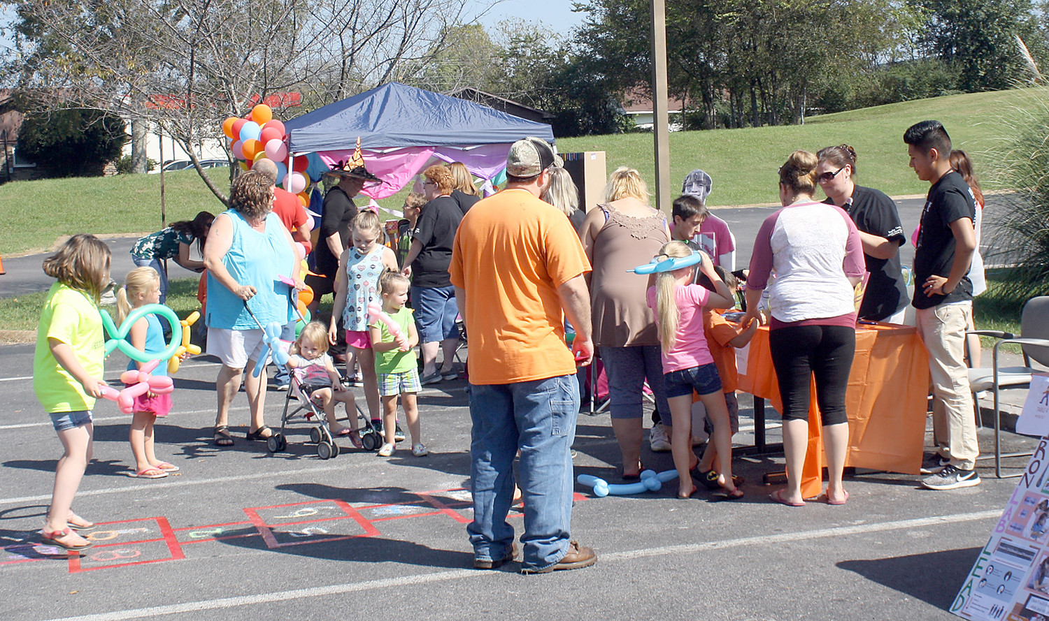 A SMALL CROWD gathered early at Friday's Fall Festival. Under the small tent to the right was Kim Morrison making balloon animals. The second booth had information on the health department's WIC Program.