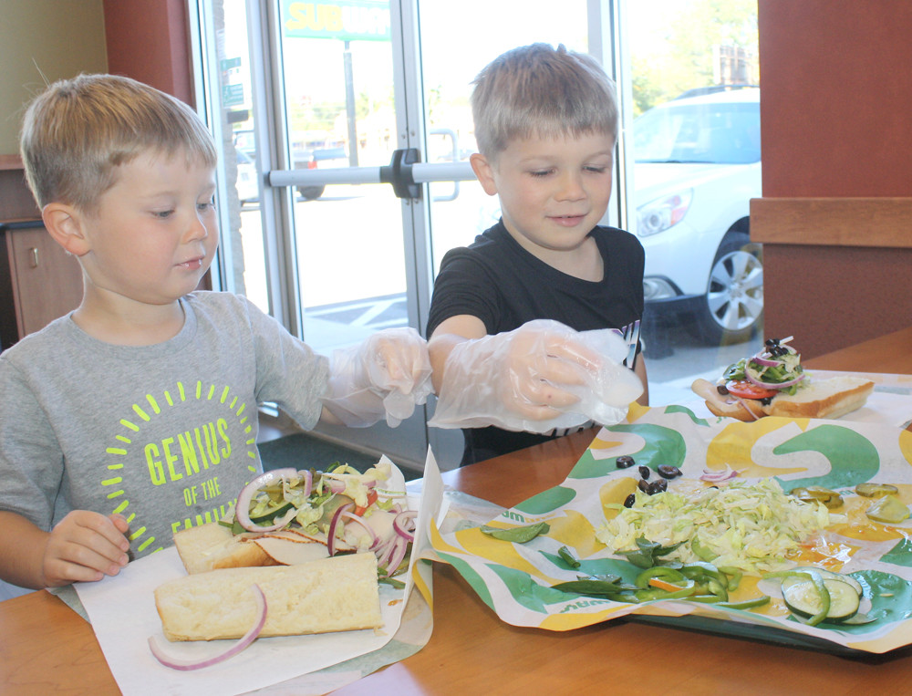 OWEN AND NOAH CULBERSON select some healthy ingredients for the Subway sandwich they were building Monday in a childrens' promotion at the new restaurant on 25th Street.