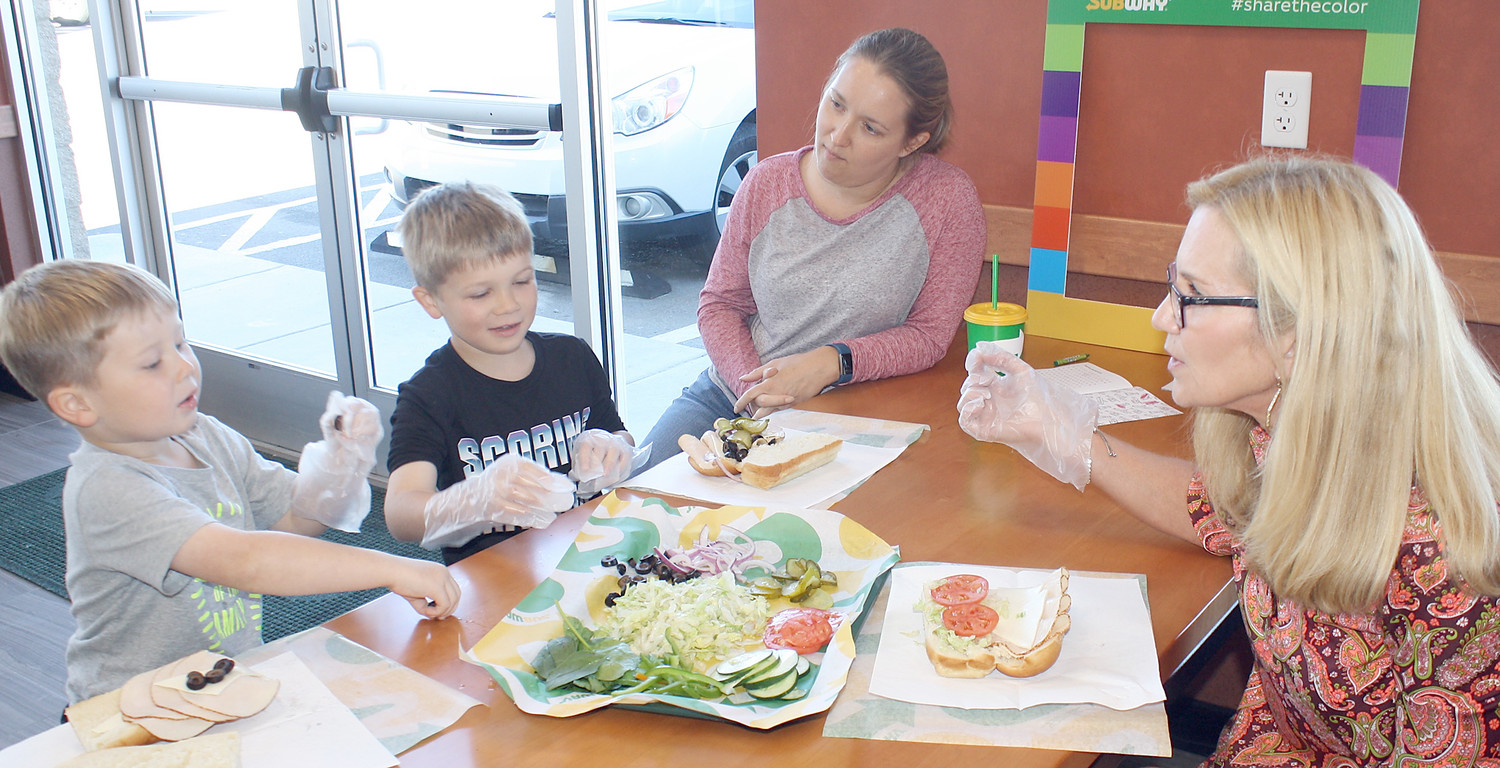 LEARNING ABOUT food and healthy eating Monday were youngsters Owen and Noah Culberson, left. Mom Emily was watching as registered dietician Laurie McGuire conducted a lesson about the colorful vegetables to be used in the boys' sandwiches.