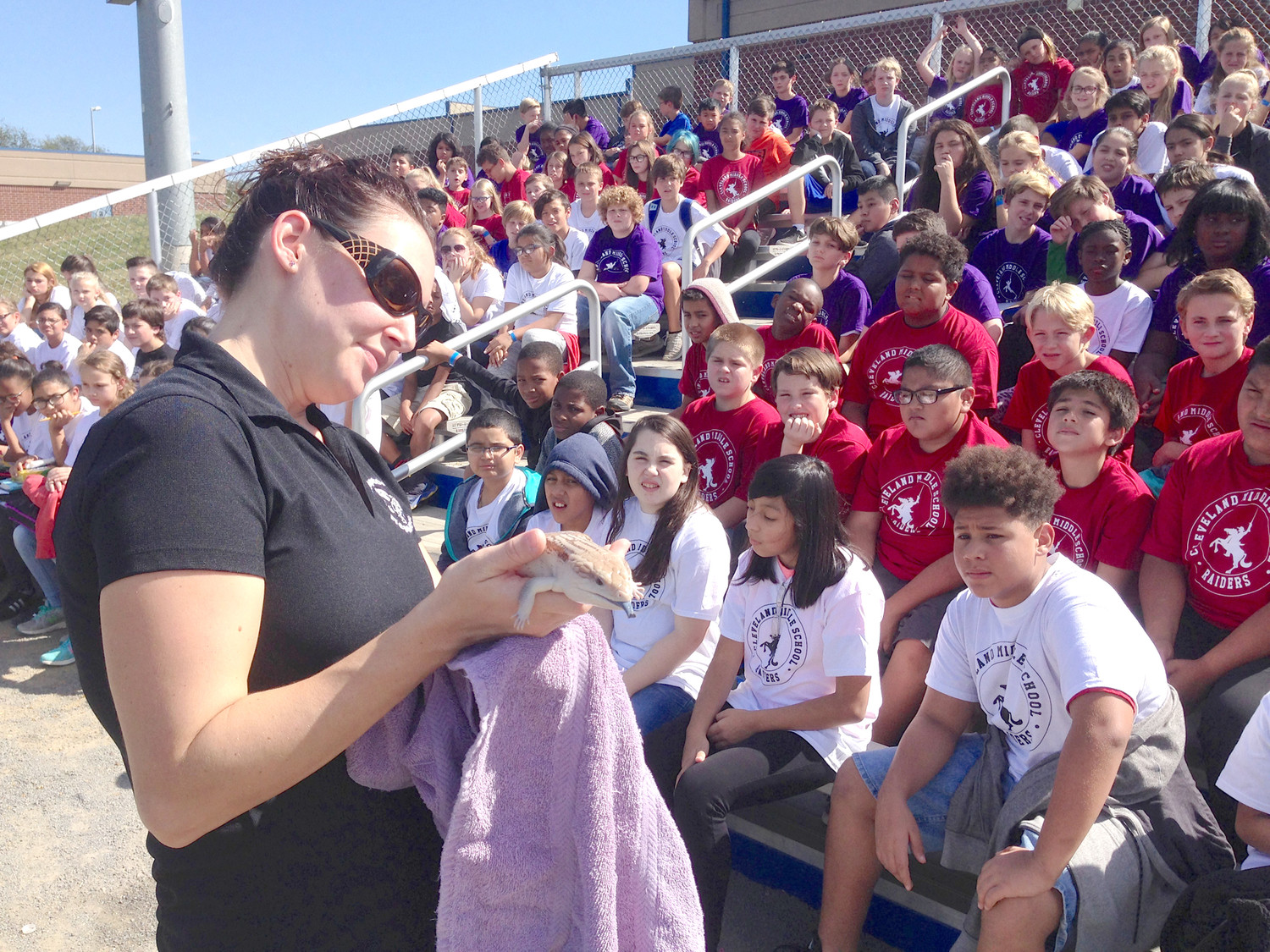 MISHALA MUNDALL of Raptors and Reptiles teaches Cleveland Middle School students about a blue-tongued skink during a recent visit to the school.