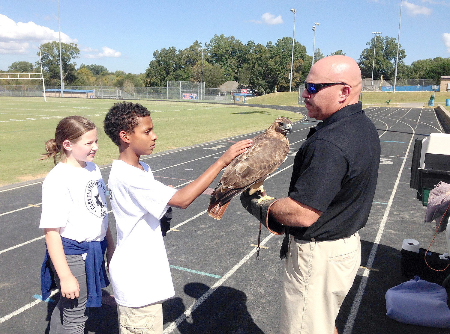 DOUG BOUCHER of Raptors and Reptiles holds a red-tailed hawk for a couple students to pet during a recent presentation at Cleveland Middle School.
