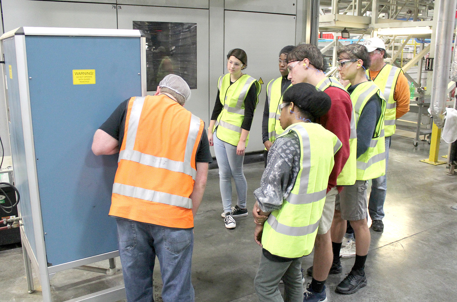 TAKING A CLOSE LOOK at the controls for a large piece of machinery at Southeastern Container, a group of Cleveland High School students take part in their Manufacturing Week tour.