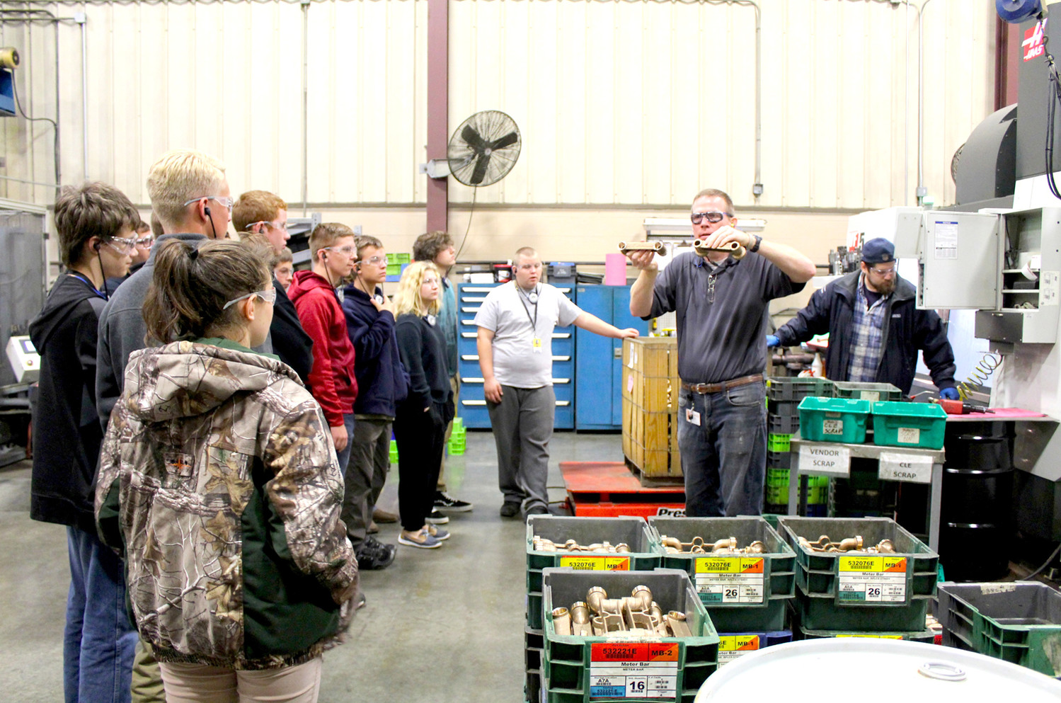 EXPLAINING how products are made and used, Rodney Hodges leads a group of Bradley Central High School students on a tour of Mueller Co. during Manufacturing Week.