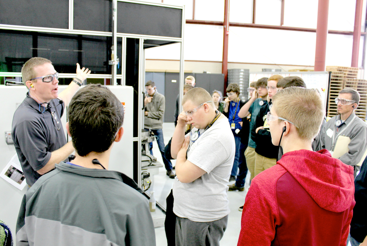 RODNEY HODGES of Mueller Co., left, teaches a group of Bradley Central High School students about the robot housed in the black box nearby. The class and company were paired together for Manufacturing Week.