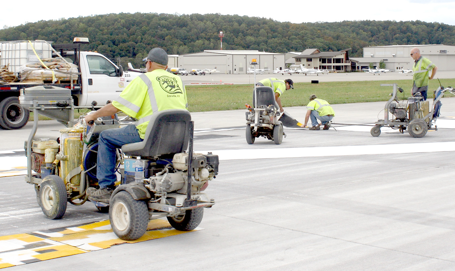 HINKLE CONSTRUCTION workers were busy Sunday laying threshold markings and numbers for the Cleveland Jetport's new runway extension. The 700-foot construction project is lengthening the landing/departure surface to 6,200 feet. The Jetport terminal is in the background.