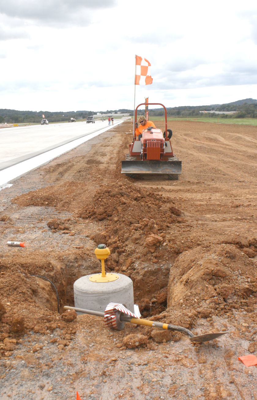 A CONSTRUCTION worker was busy with some final grading work Sunday on the new runway extension at the Cleveland Jetport. The light in the foreground is at the end of the runway extension.