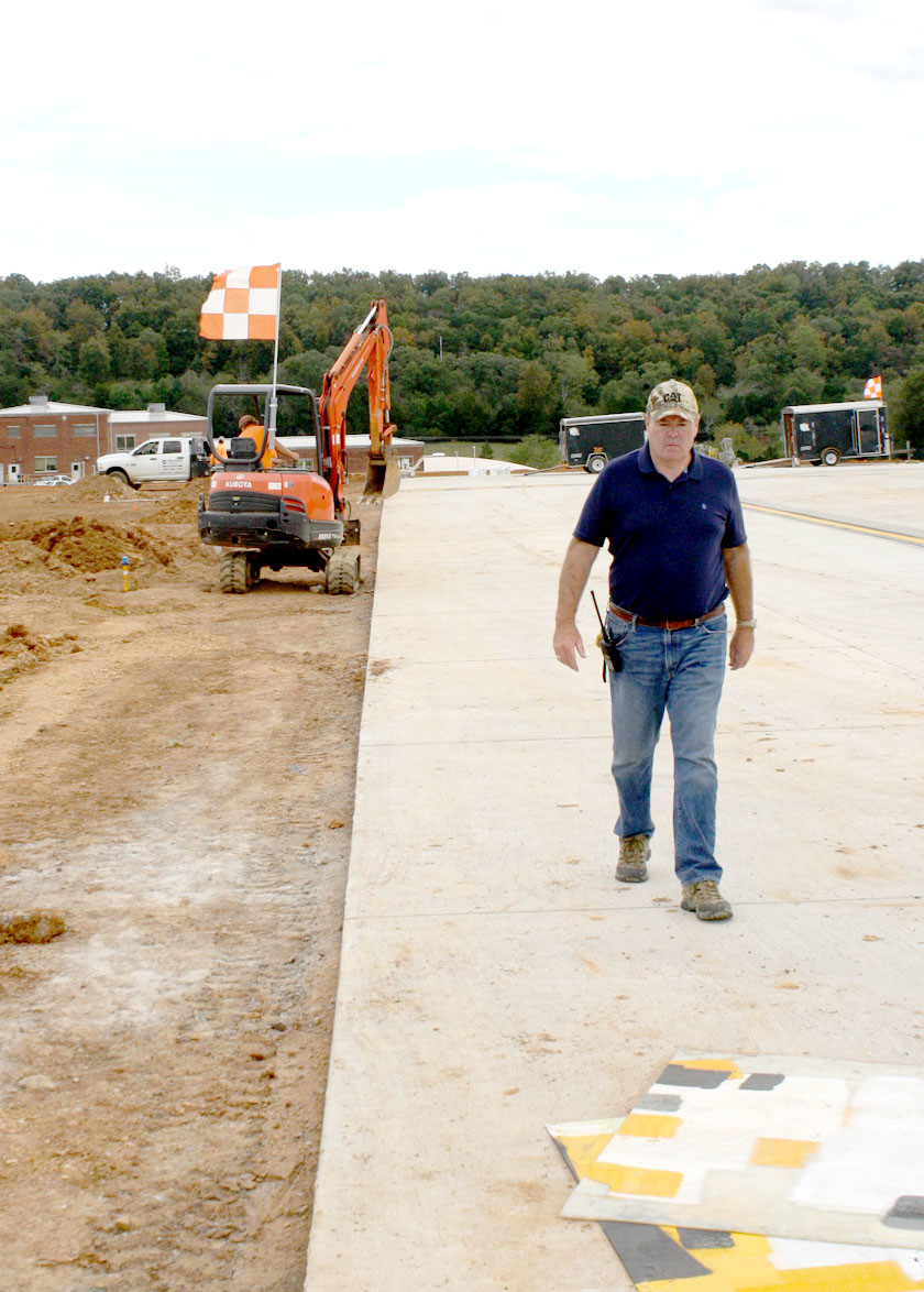 CLEVELAND JETPORT Manager Mark Fidler is shown walking away from a couple of Hinkle construction workers Sunday. The crew was installing lights at the end of the taxiway on the new runway extension.