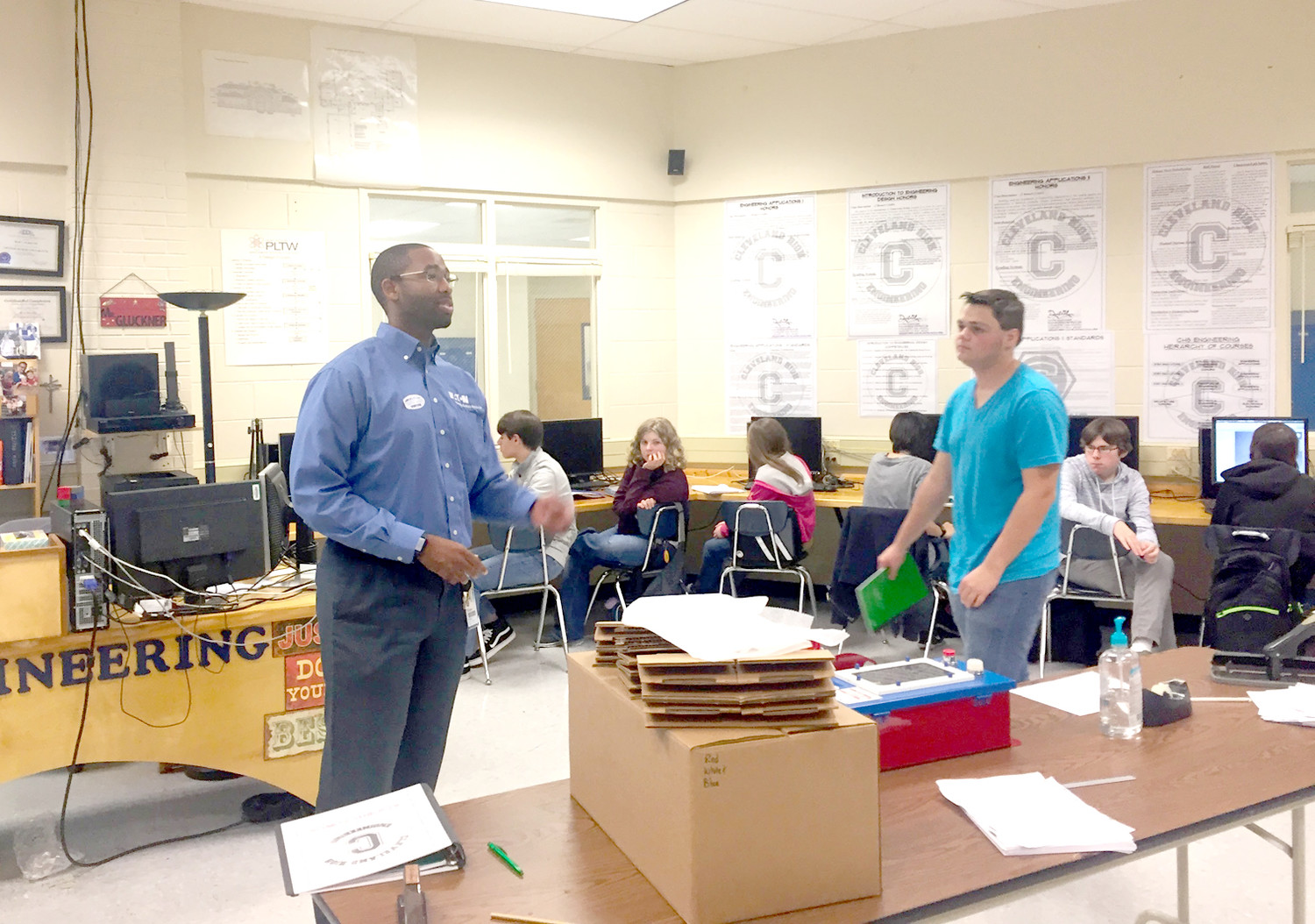MICHAEL PATTERSON of Eaton Electrical speaks to students in David Glockner's class at Cleveland High School about a project they were about to do for Cleveland Associated Industries' Manufacturing Week.