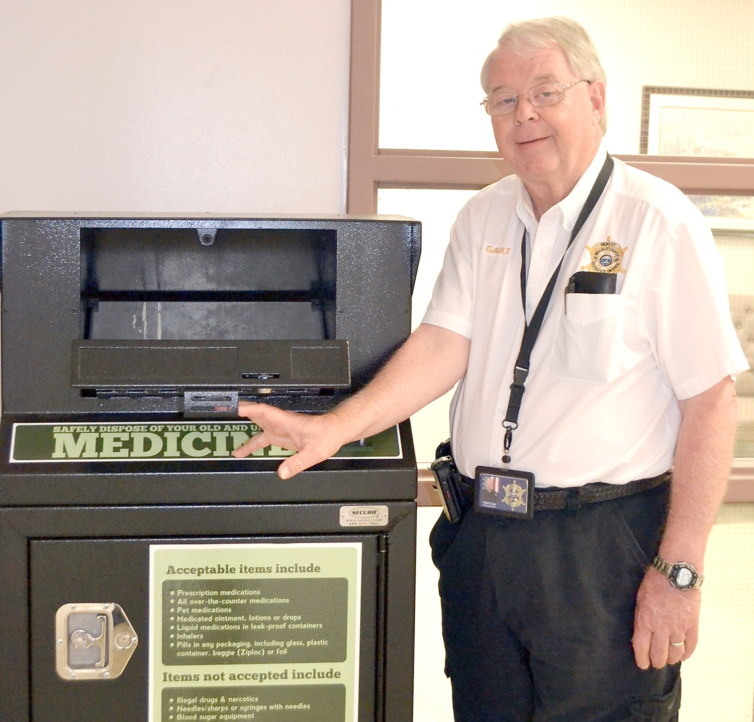 BOB GAULT of the Bradley County Sheriff's Department stands with the drug-take back deposit box at the BCSO on Blythe Avenue.