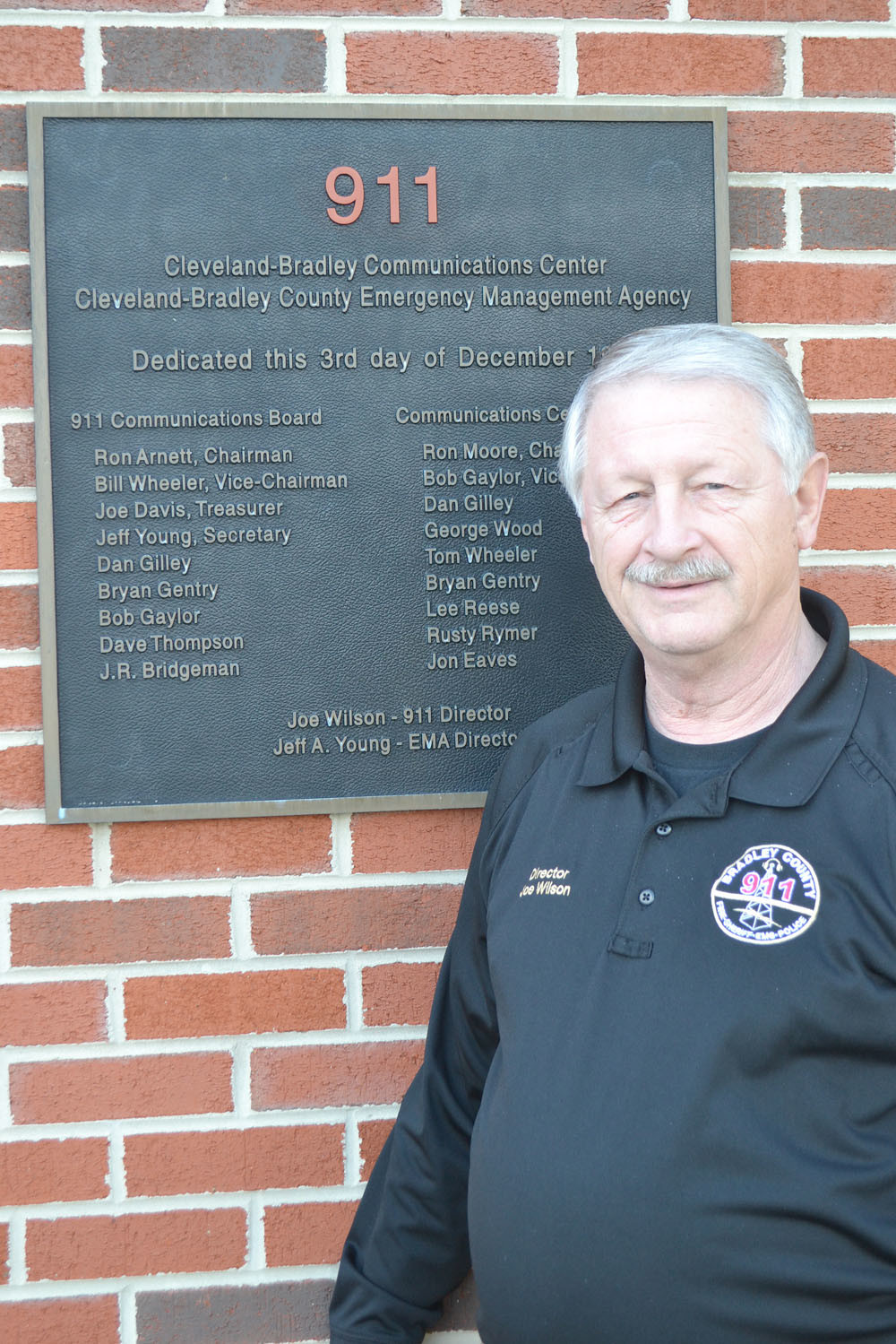 JOE WILSON stands at the dedication plaque outside the 911 center. The plaque includes the names of the county commissioners and members of the consolidated communication center.