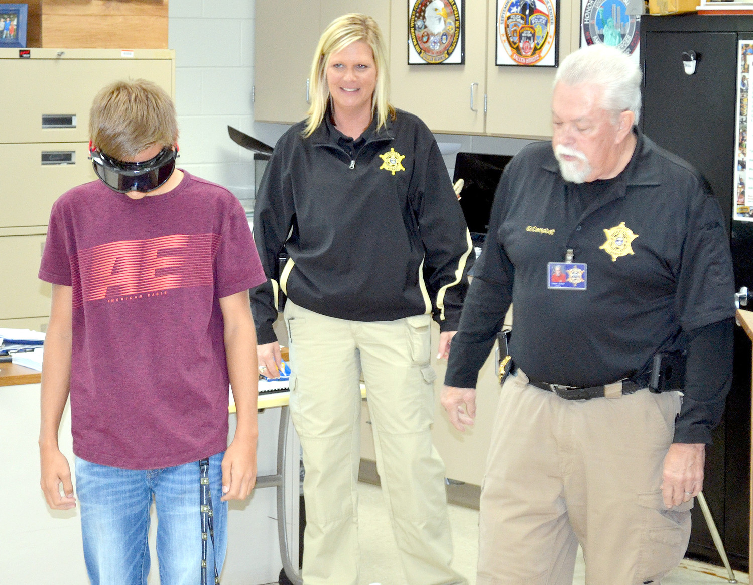 A Walker Valley High School student attempts the one leg stand field sobriety test with Lt. Julie Quinn, center, and Deputy George Campbell.