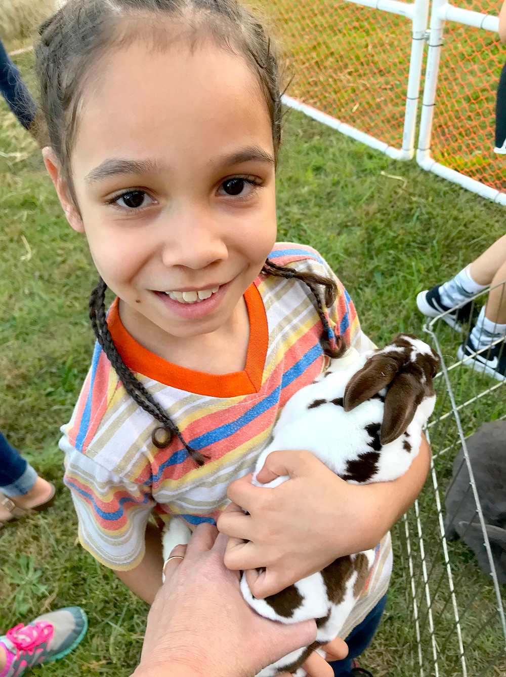 LASHAWN HARTUNG cuddles a bunny rabbit from the Little Country Farm and Petting Zoo during Blythe-Bower Elementary School's recent fall festival.