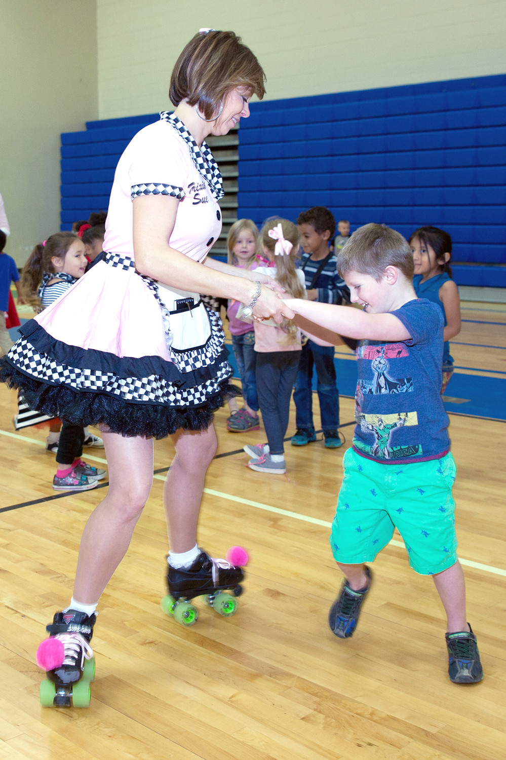 ERIN COLE, left,  glides around on her roller skates with student Luke Wilson at the Mayfield Elementary celebration of the 1950s.