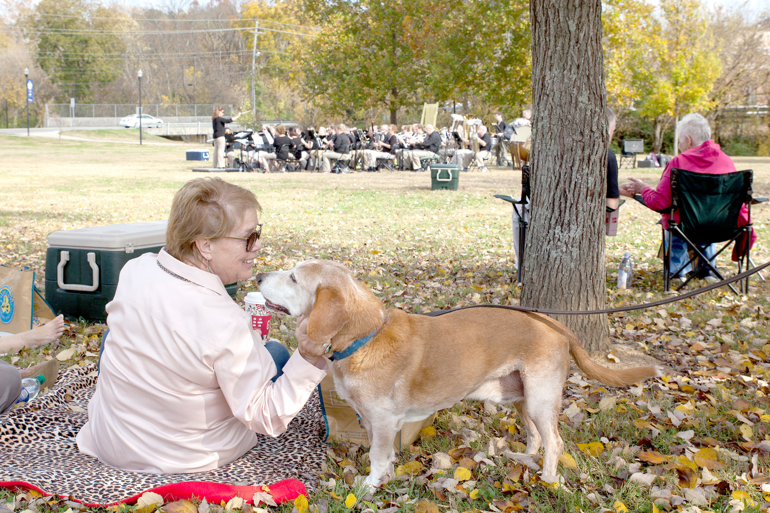 ONE OF THE ATTENDEES of the Cleveland 175th celebration makes a four-legged friend while listening to the Cleveland Pops perform on Sunday.