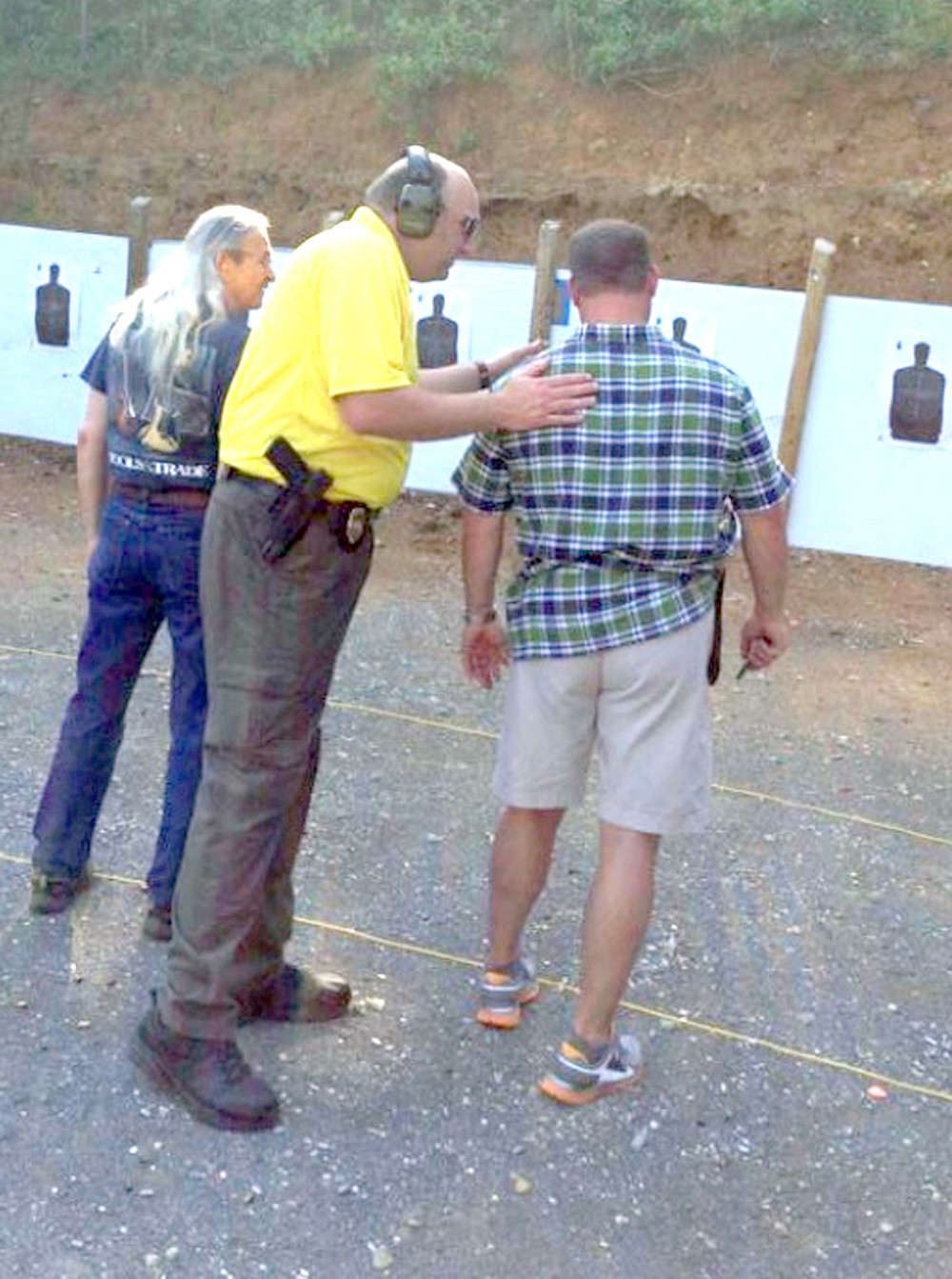 SHERIFF ERIC WATSON, center, assists during a firing range class. The sheriff has announced the next set of church security training opportunities next year will include firearms training.