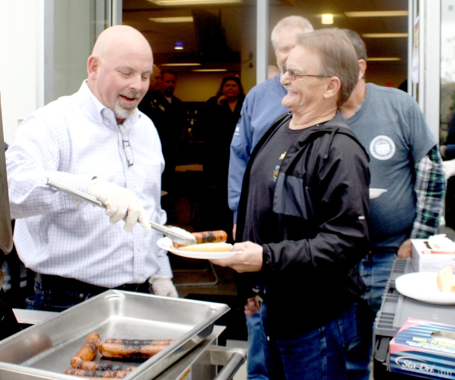 WHIRLPOOL CLEVELAND employee and veteran Gordon Heughan, right center, shares a laugh with Plant Manager Dicky Walters on Thursday. The Cleveland facility treated its 51 veterans to a luncheon cookout and a 21-gun salute by the Bradley County Funeral Honor Guard.