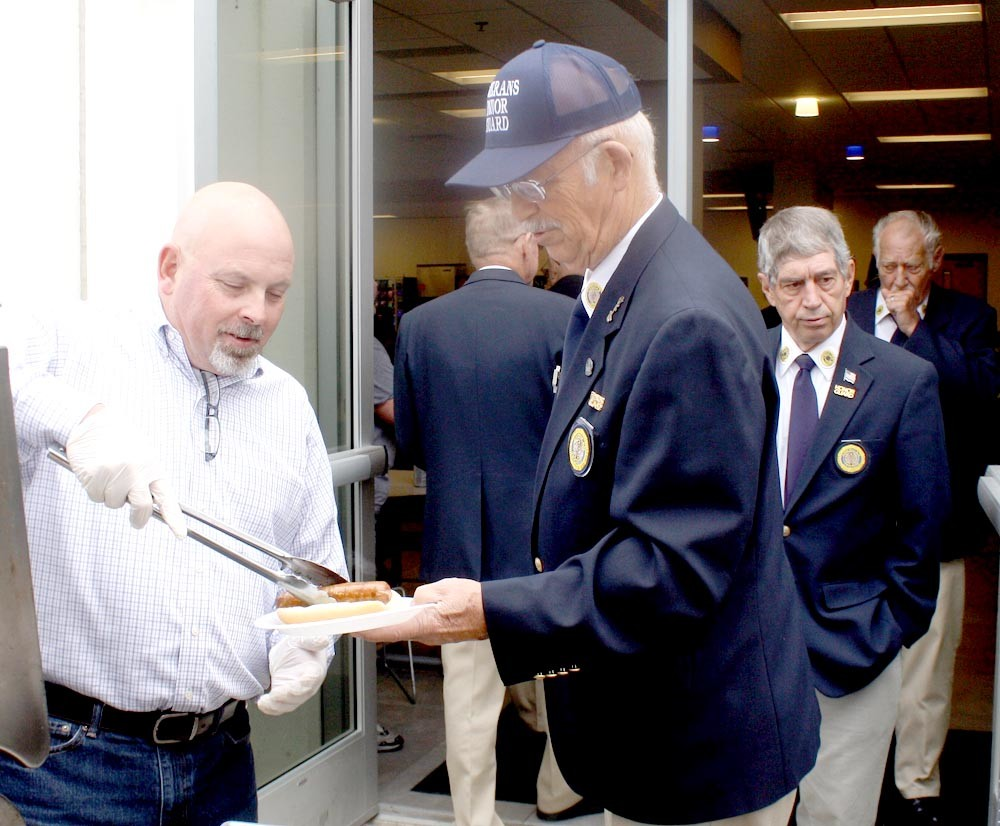 WHIRLPOOL PLANT Manager Dicky Walters, left, is shown serving hot dogs to members of the Bradley County Funeral Honor Guard. Accepting one is guard member John Thomason.