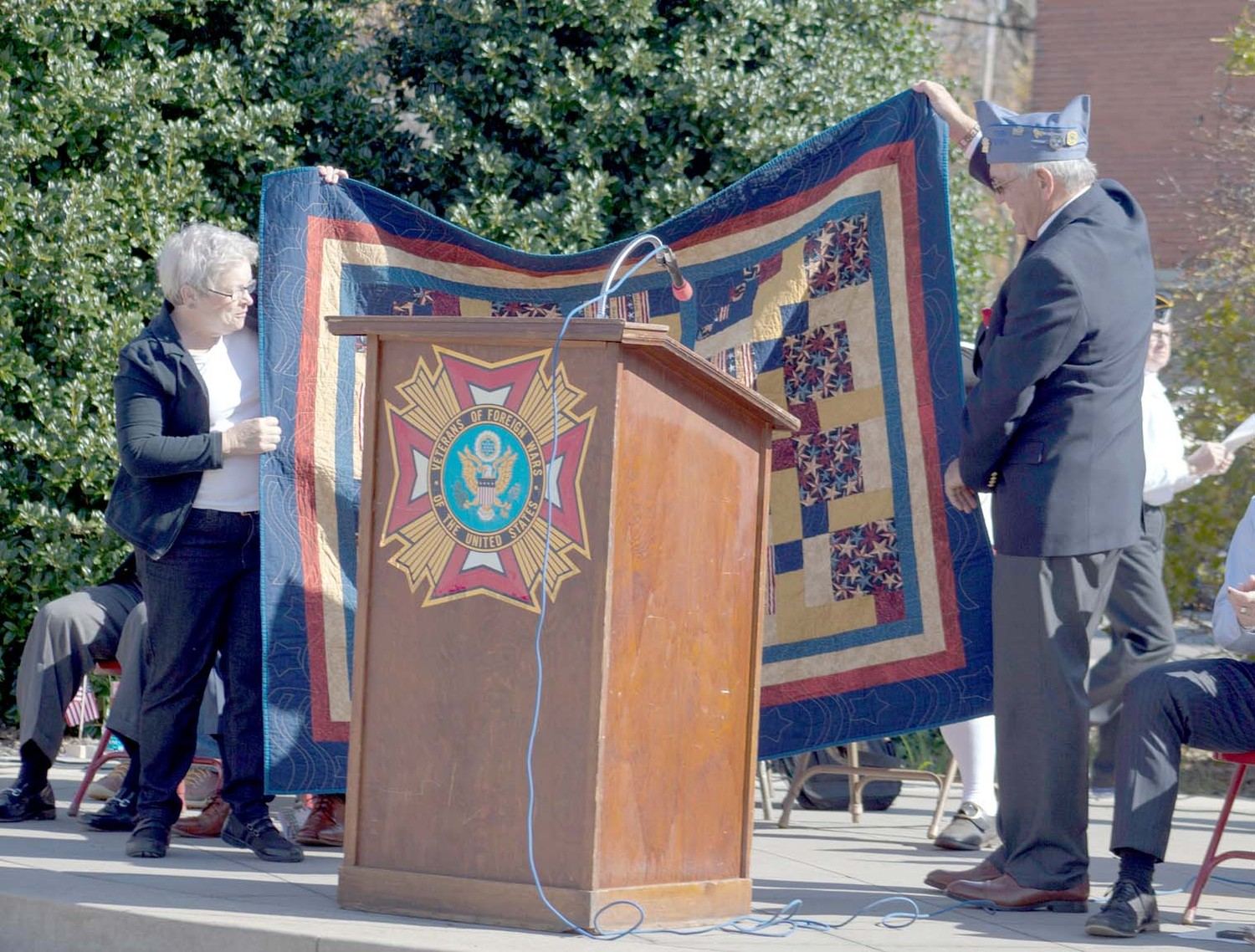 KATHAY PEGRAM, left, presents Donnie Hancock, commander of American Legion Post 81, with the Quilt of Valor on behalf of the Cherokee Blossom Quilt Guild.