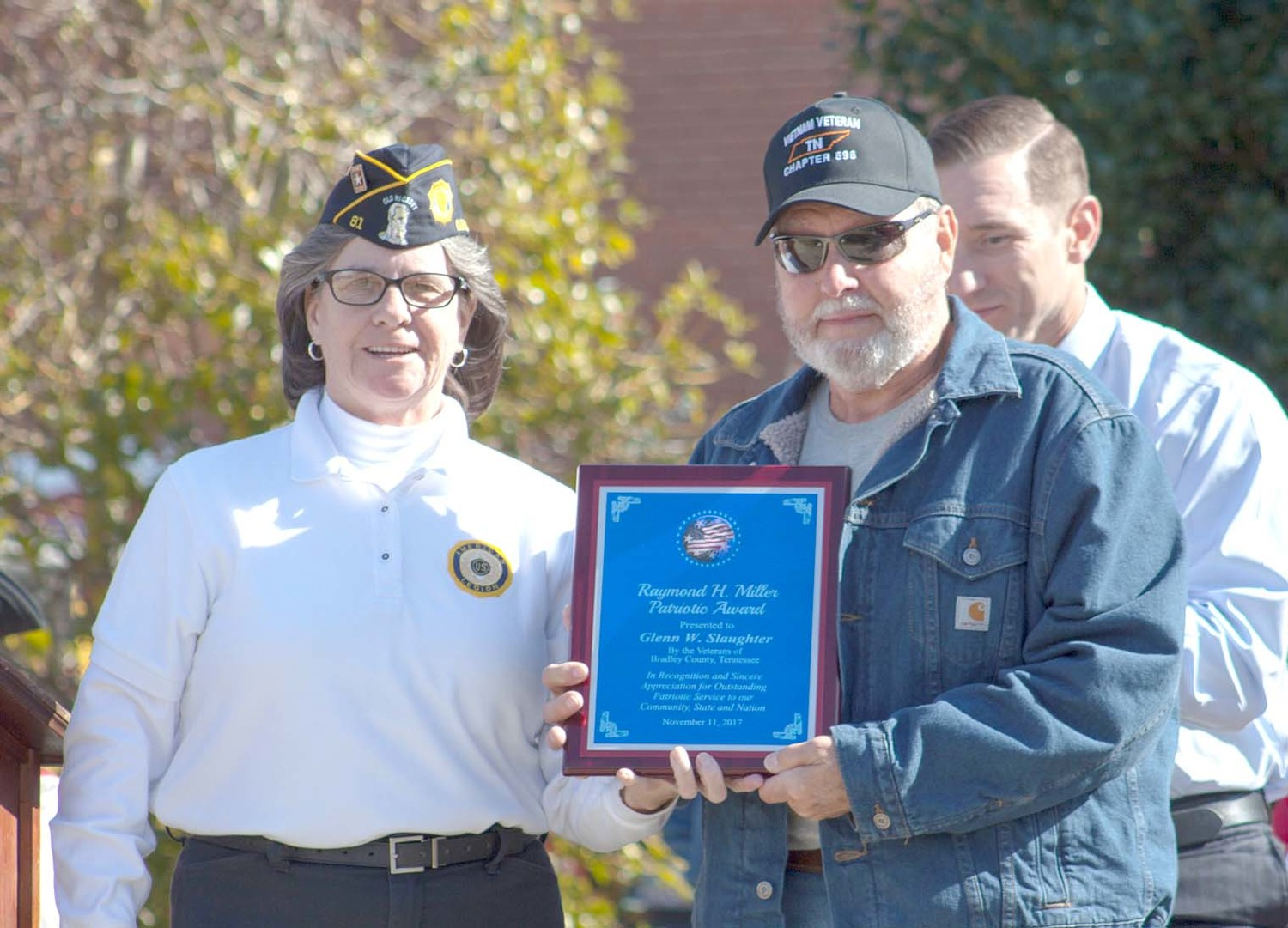 GLENN SLAUGHTER, right, was presented a plaque by Mary Baier, on behalf of Bradley County veterans organizations. Slaughter was presented the Raymond H. Miller Patriotic Award for his service to veterans and veteran organizations. He is the seventh recipient of the award.