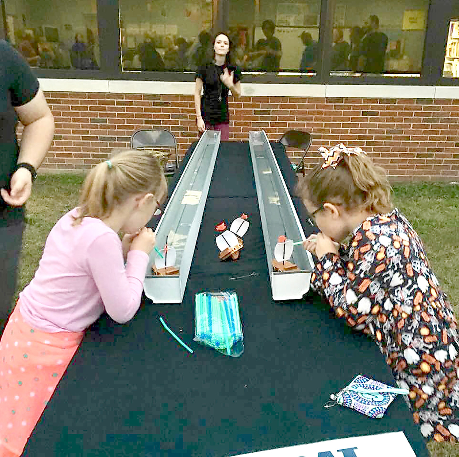 BLOWING their boats to the finish line, two Michigan Avenue Elementary third-graders compete in the boat races at the school's Fall Festival.
