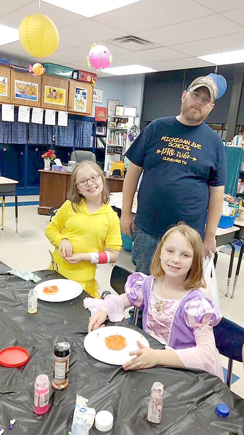 ABBY and LUCY TRAUNERO enjoy cookie decorating with their dad, Matt, during the Michigan Avenue Elementary Fall Festival. He is parent volunteer who helped set up the activities.