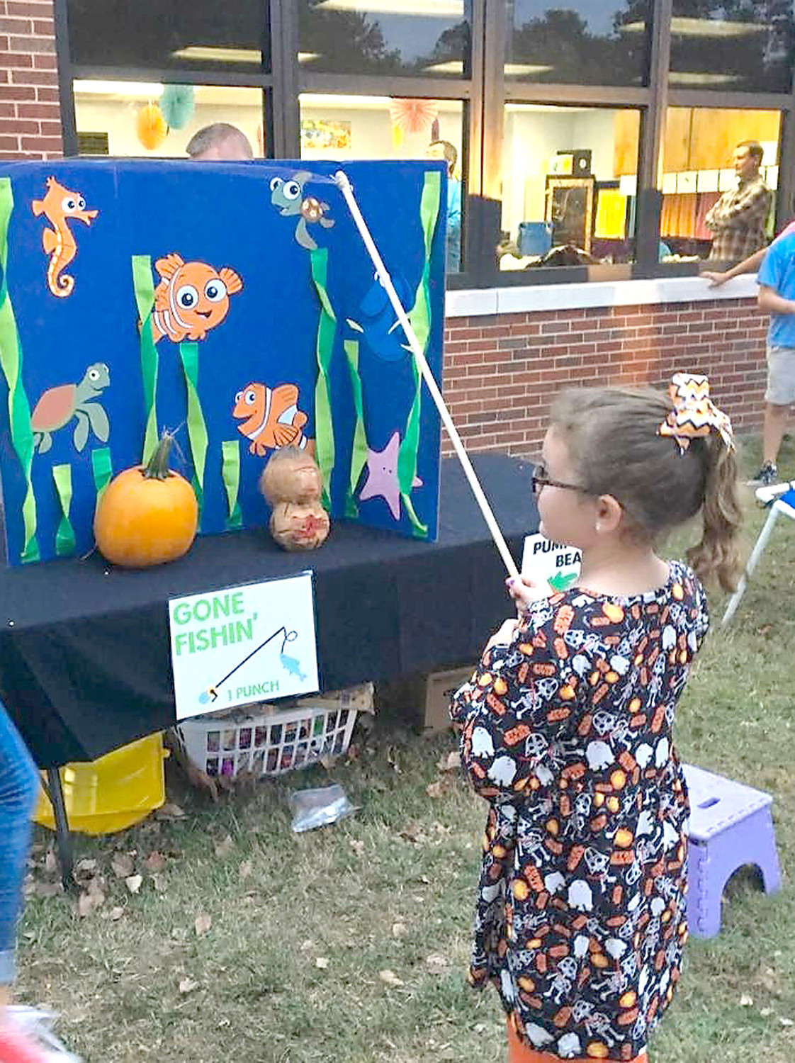 GENEVIEVE OWENS waits patiently to see what she caught while fishing during Michigan Avenue Elementary's Fall Festival.