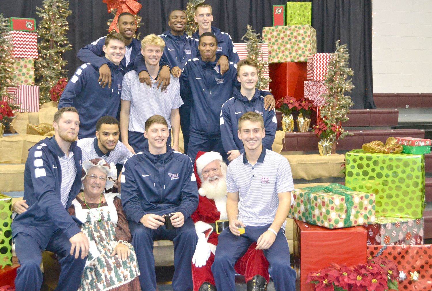 THE LEE UNIVERSITY men's basketball team posed for a team show with Santa Claus and Mrs. Claus, at Monday's Operation Christmas Child shoebox packing.