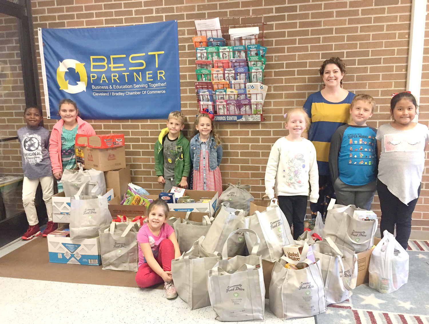 "STUDENTS at Yates Primary School collected food to help support  Southern Heritage Bank's ""Cleveland Helping Cleveland"" food drive. Several students are shown with bags overflowing with food."