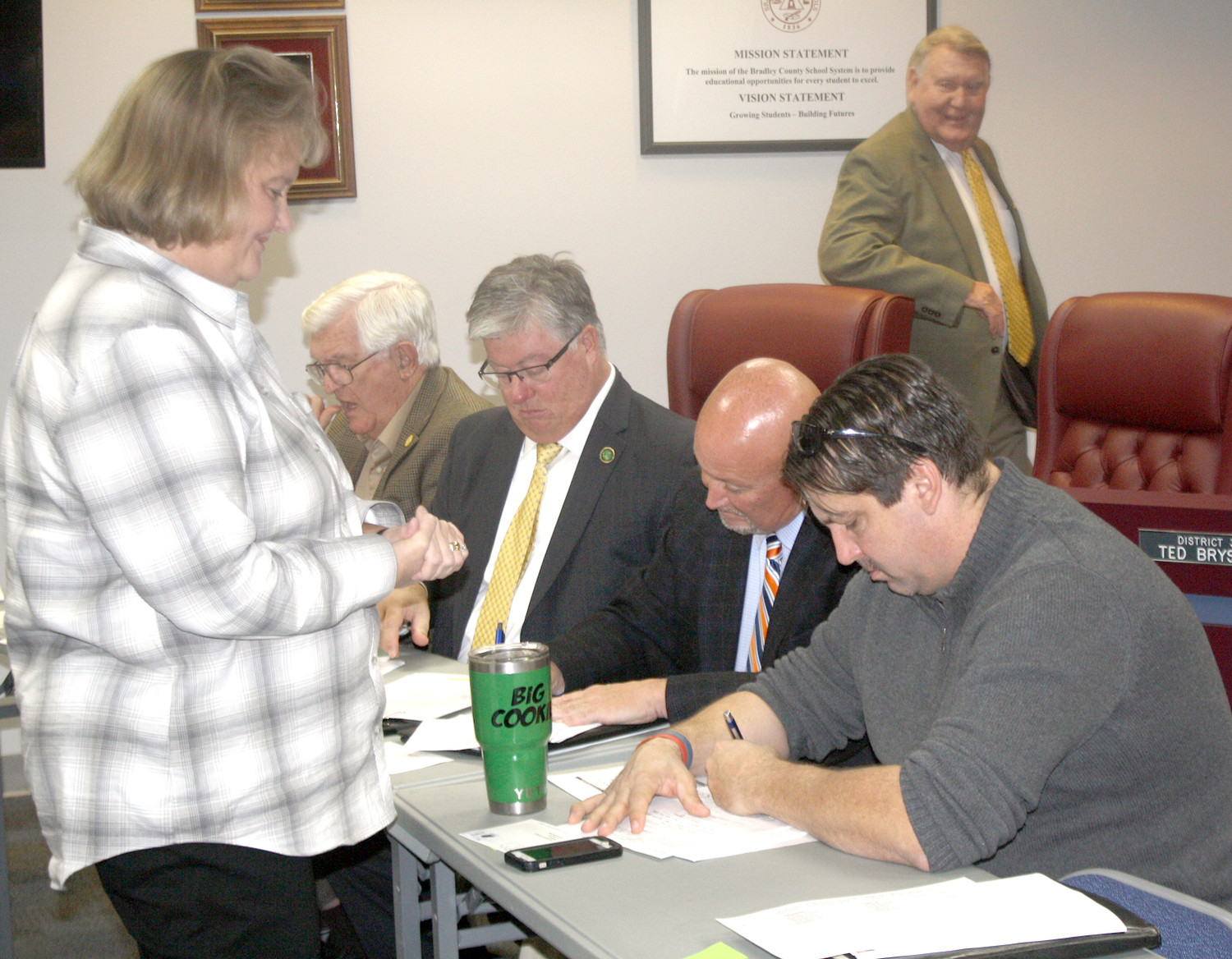 BRADLEY COUNTY COURT Clerk Donna Simpson, left, talks with a group of commissioners before Monday's meeting in the school system's meeting room. Commission members include, seated  from left, Tom Crye, Milan Blake, Johnny Mull and Jeff Yarber, with Commission Chairman Louie Alford standing in back.