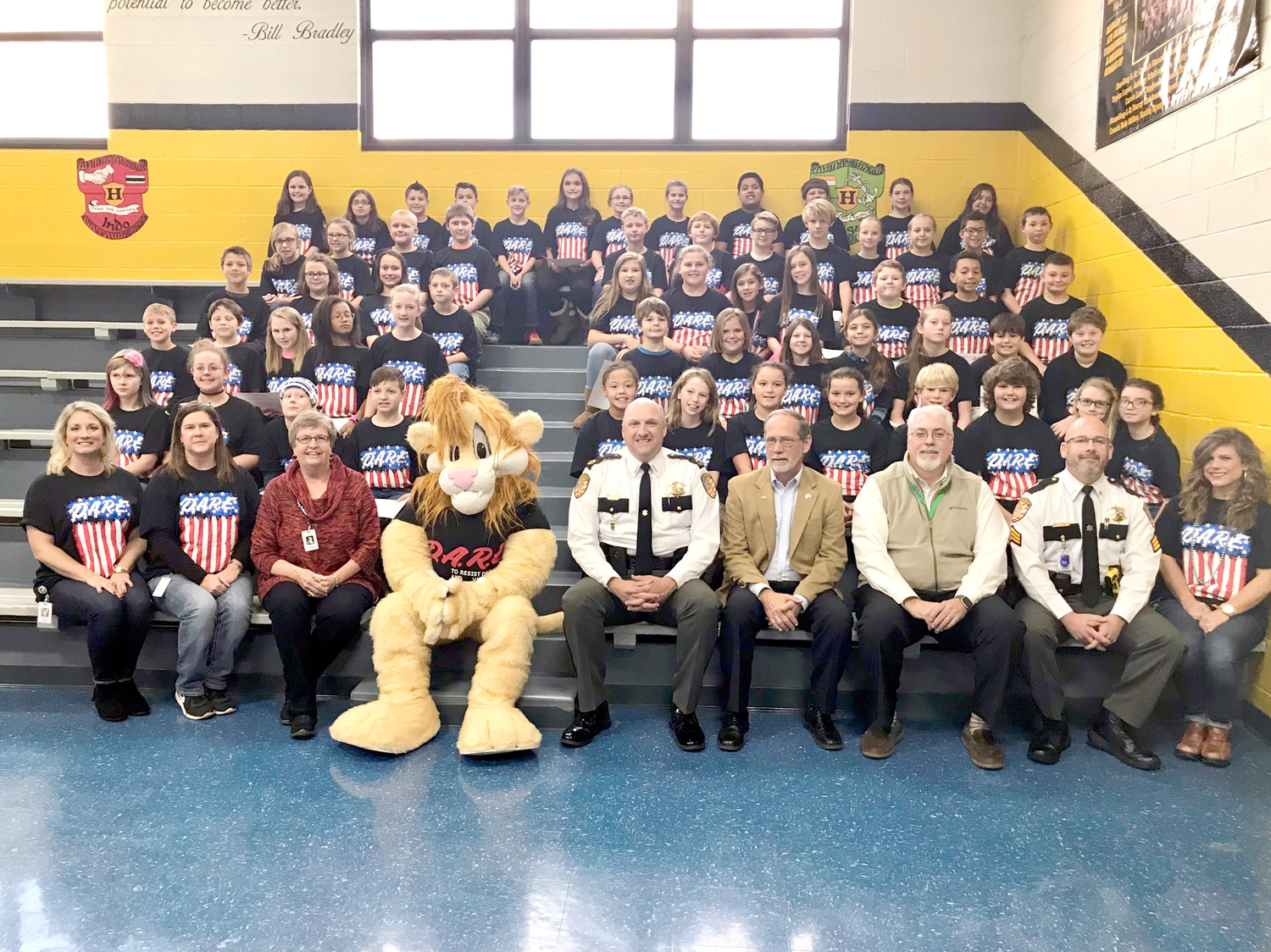 THE BRADLEY COUNTY SHERIFF'S OFFICE held a graduation ceremony at Hopewell Elementary School to honor fifth-graders who completed the DARE program, which was taught by their school resource officer, Sergeant Mitchell Roe. Each student submitted an essay at the conclusion of the program, and the best essay was chosen from each of the three classes. The best essay winners were George Emendorfer, Abrt Whitaker and Jaxson Humble. Those students read their essays during the ceremony, and were presented a medal from Sheriff Eric Watson, Bradley County School Board Member Nancy Casson, Roe, and Principal Tim Riggs. From left (in the bottom photo) are, front row: Emendorfer, Whitaker and Humble; back row: Roe, Bradley County Mayor D. Gary Davis, Darren the Lion (DARE mascot), Watson, Riggs and Casson.