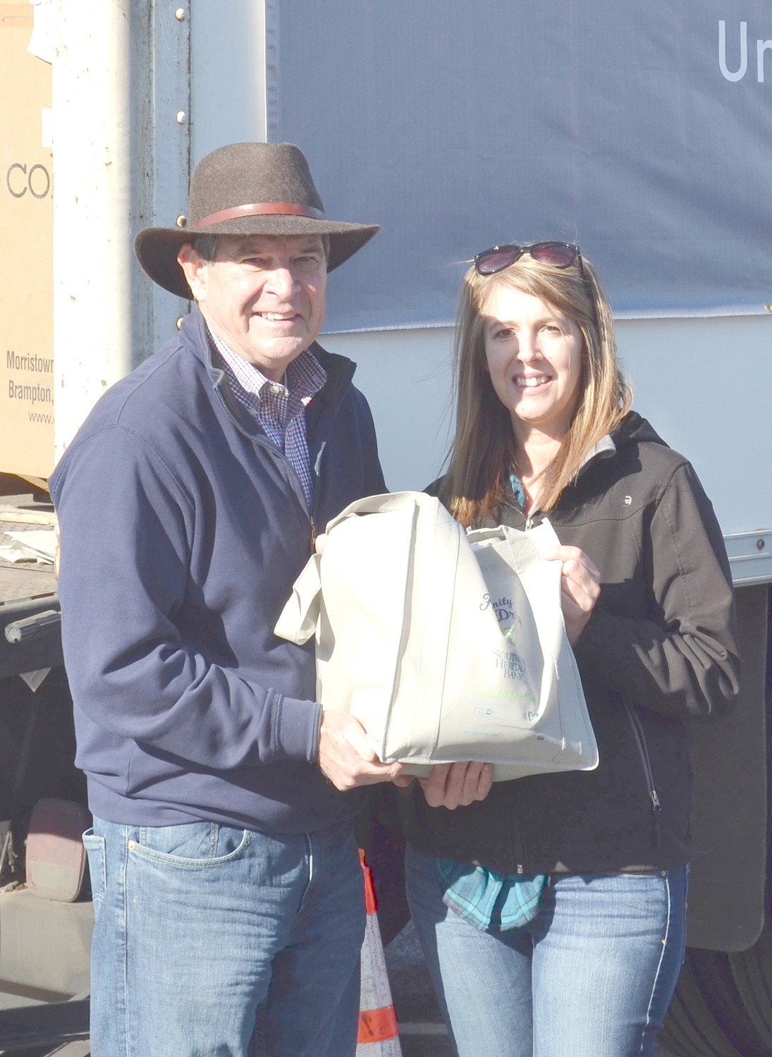 Lee Stewart accepts food drive donations from  Lori Burmeister of Eaton Corporation.