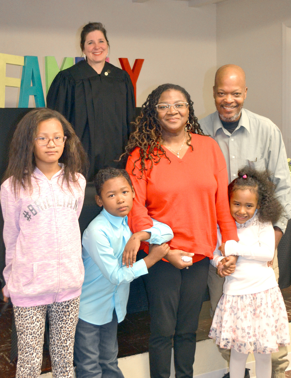 THE ROGERS FAMILY has a full family after adoptions on Monday. From left are, front, Ashanti, Alejandero and Mariela, and back, Chancellor Jerri Bryant, and parents Veronica and Walter Rogers.