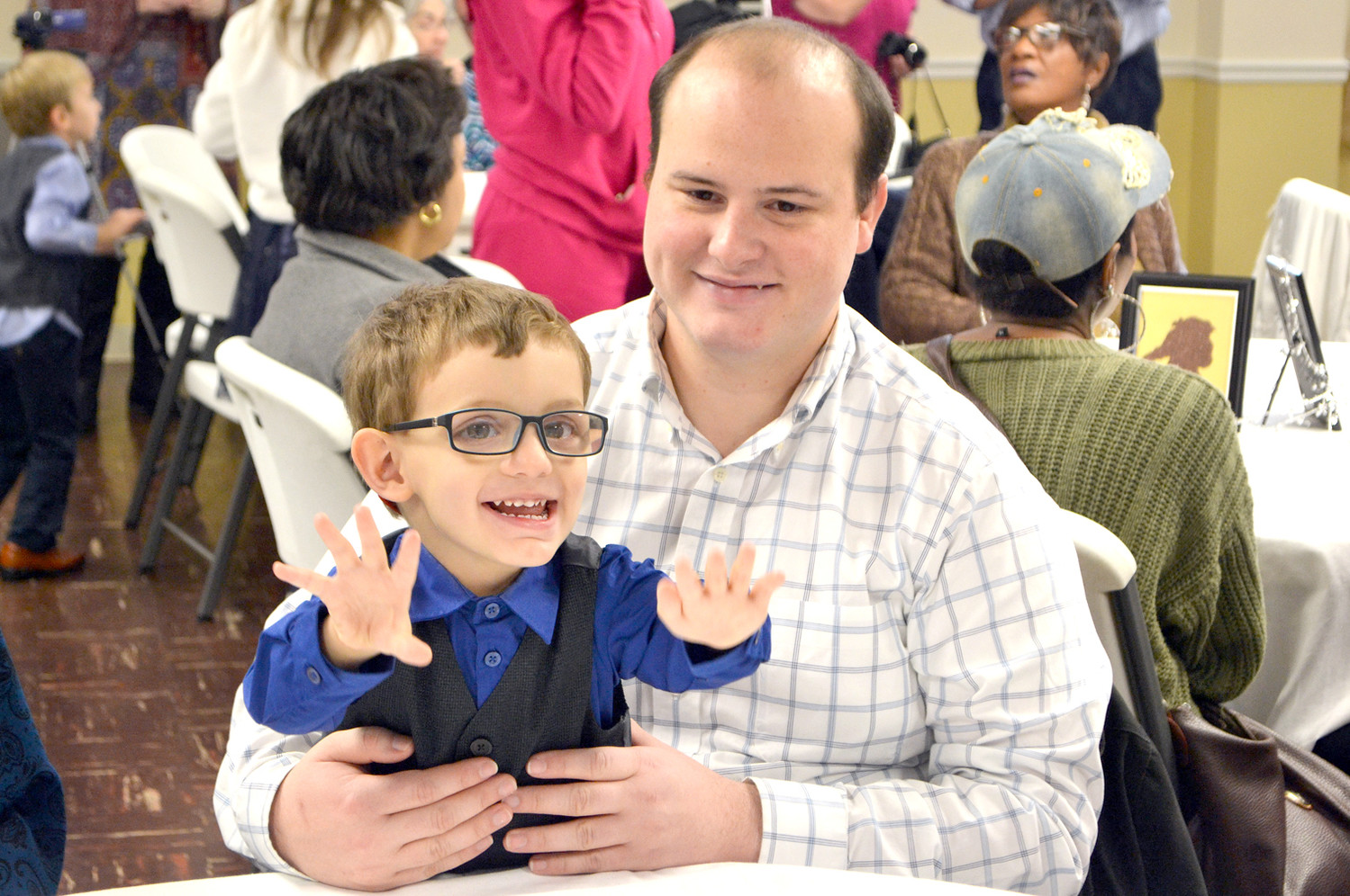 TWO-YEAR-OLD David Inman was adopted during the National Adoption Day ceremonies on Monday. He is sitting in his uncle Christopher's lap as he reaches for his new parents.