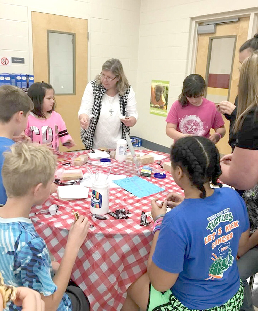 CHRISTEL PANKEY, parent of a first-grade student, helps students make s'mores during a  camping-themed literacy night at Park View Elementary School.