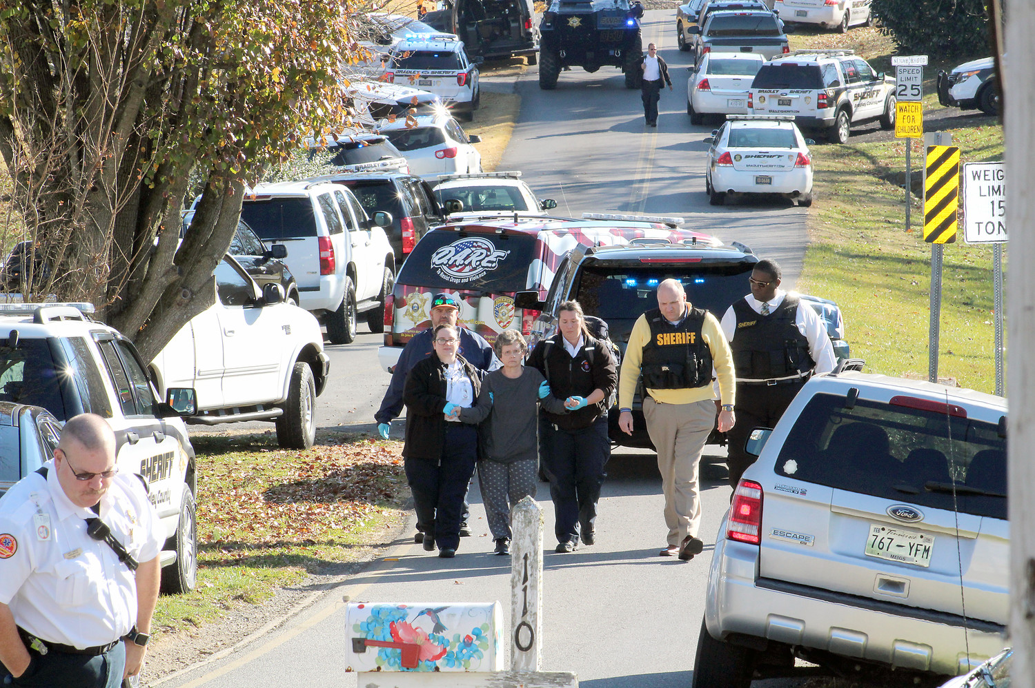 LAW ENFORCEMENT and emergency responders are seen escorting a Royal Oaks subdivision homeowner away from her residence after a hostage crisis on Tuesday. She escaped her home after it had been invaded by a couple she had reported to be in a suspicious vehicle in the neighborhood. The two were finally placed in custody after a six-hour standoff. Seen at right are Sheriff Eric Watson and BCSO Public Information Officer James Bradford.