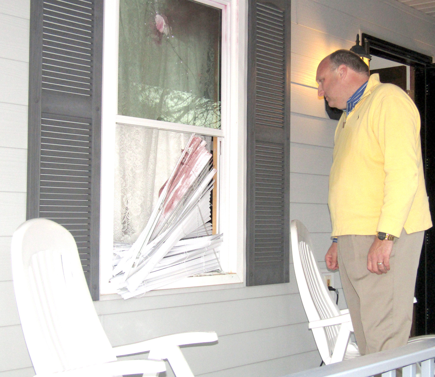 SHERIFF ERIC WATSON shows where a couple smashed through the front window of a Royal Oaks subdivision residence. The stains on the window blinds are from the tear gas that was used to flush out the pair of home invaders, who had barricaded themselves inside.