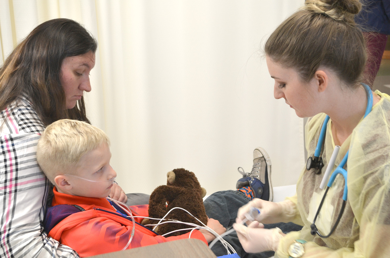 SIX-YEAR-OLD Elijah Bean is observed by RN student Bailey Davis during the mass casualty drill held Wednesday at Lee University's School of Nursing. Holding Elijah is his mother, Sherry Bean.